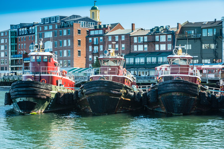 Portsmouth, ME, USA - October 6, 2015: A small fleet of tugboats is moored in the harbor in Portsmouth, New Hampshire.