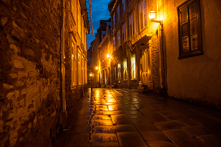 Lamplights cast an eerie golden glow on the rainy night streets of Old Quebec City, Canada.