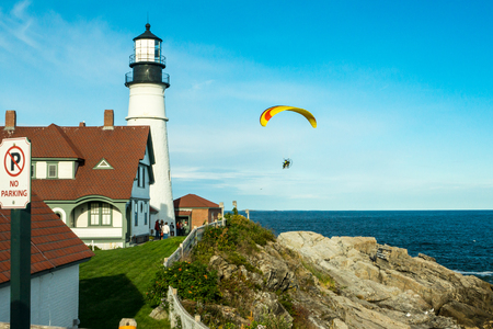 A modern fan-powered parachute  or kite sails through the sky above historic Portland Haed Lighthouse, providing a stark contrast between old and new technology. Banco de Imagens