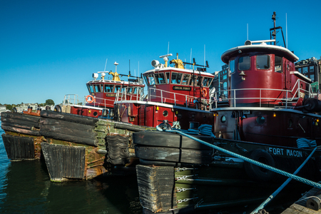 Portsmouth, Maine, USA - October 6, 2015: The fleet of famous Moran tugboats stand shipshape and ready under blue skies as a hurricane approaches.