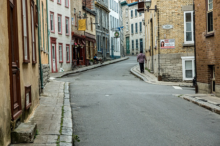 Quebec, Canada - Spetember 11, 2015: A man walks the deserted, European style streets of Quebec City in the early, pre-dawn light. 新聞圖片