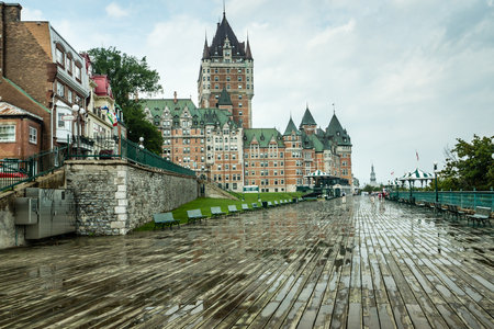 Quebec City, Quebec, Canada - Sept.9, 2015: Chateau Frontenac, a landmark hotel, towers over the boardwalk beside the St. Lawrence seaway as visitors stroll after a rain shower.
