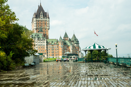 seaway: Quebec City, Quebec, Canada - Sept.9, 2015: Chateau Frontenac, a landmark hotel, towers over the boardwalk beside the St. Lawrence seaway as visitors stroll after a rain shower.