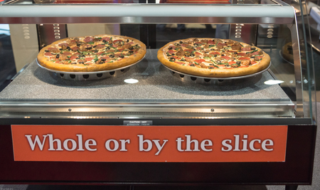 Fresh oven baked pizza, whole or by the display at a warming display.