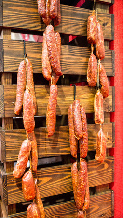 Authentic Italian Pepperoni sausages hanging on a wooded wall 版權商用圖片 - 56240541
