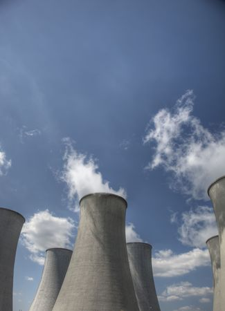 Nuclear cooling towers emitting steam with blue sky photo