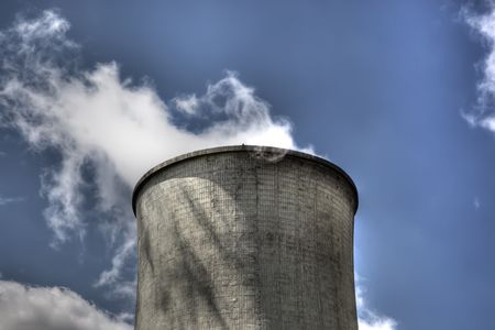 Nuclear cooling tower with emitting steam again blue sky photo