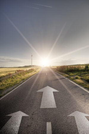 vision concept: Asphalt road with arrows seeking ahead for sun Stock Photo