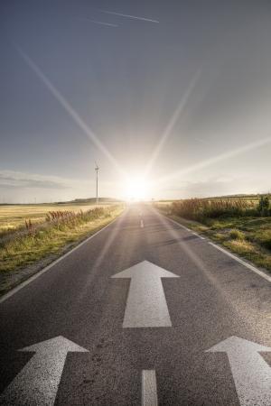 mission: Asphalt road with arrows seeking ahead for sun Stock Photo
