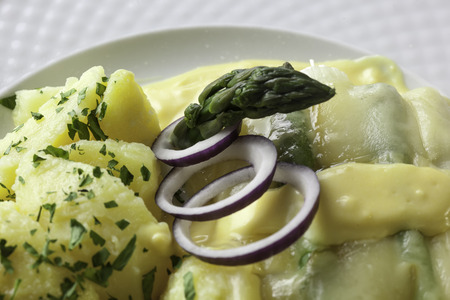 buttered: Asparagus baked with cheese served with buttered potatoes  Stock Photo