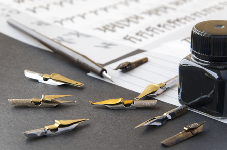 tipped: calligraphy pen tips , flat tipped nib, black ink bottle and practice sheets on the table