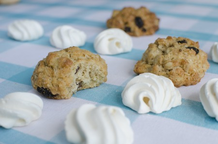 kiss biscuits: Close-up of fresh white meringue and cookies on a blue tablecloth