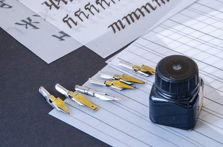 ink bottle: calligraphy pen tips , flat tipped nib, black ink bottle and practice sheets on the table