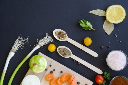 vegetarian food: Fresh delicious ingredients and spices on a wooden spoon for healthy cooking on dark black background and wooden cutting board, top view, banner. Diet or vegetarian food concept.