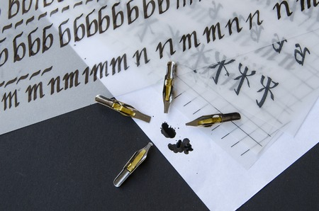 tipped: calligraphy pen tips , flat tipped nib, black ink stans and practice sheets on the table Stock Photo