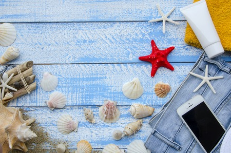 yellow star: Summer accessories - shells, mussels, sea stars on a blue wooden background. A set of basic things for a beach holiday - sunblock, towel, hat and mobile phone sticking out of a pocket of a jeans