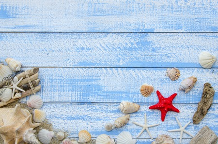 sea stars: Summer sea beach accessories - shells, mussels, sea stars and sand on a blue wooden background. Summer beach sea concept. Red sratfish in the center