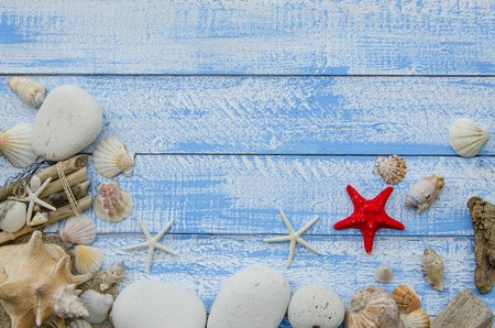 Summer sea beach accessories - white stones, shells, mussels, sea stars and sand on a blue wooden background. Summer beach sea concept. Red sratfish in the center