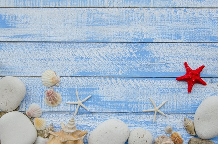 sea stars: Summer sea beach accessories - white stones, shells, mussels, sea stars and sand on a blue wooden background. Summer beach sea concept. Red sratfish in the center Stock Photo