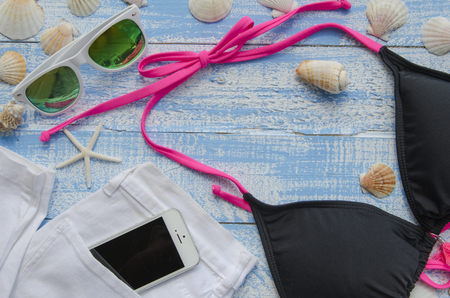 swimsuite: Summer accessories on a blue wooden background. Set of basic things for a beach holiday-mussels, sea stars, shells, starfish, sunglasses, swimsuite and mobile phone sticking out of a pocket of a jeans Stock Photo