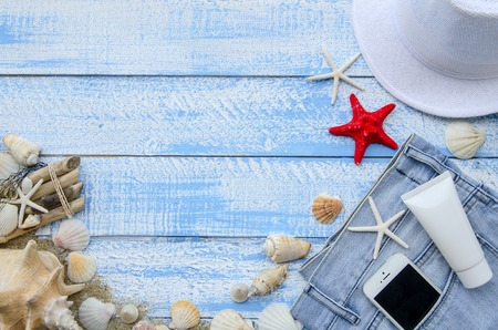 sea stars: Summer accessories - shells, mussels, sea stars on a blue wooden background. A set of basic things for a beach holiday - sunblock, towel, hat and mobile phone sticking out of a pocket of a jeans