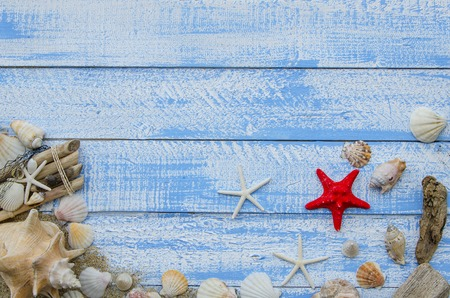 sea stars: Summer sea beach accessories - white stones, shells, mussels, sea stars and sand on a blue wooden background. Summer beach sea concept. Red starfish in the center