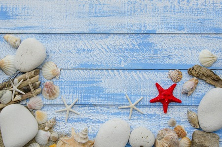 white stones: Summer sea beach accessories - white stones, shells, mussels, sea stars and sand on a blue wooden background. Summer beach sea concept. Red starfish in the center