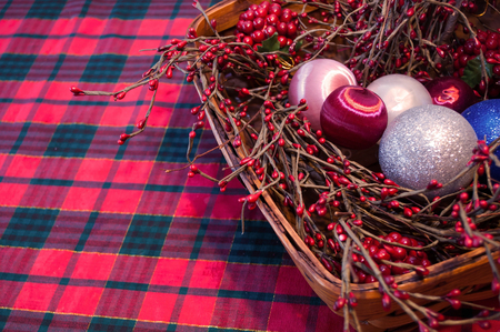 A Christmas basket filled with holly branches and tree ornaments with a plaid tablecloth background