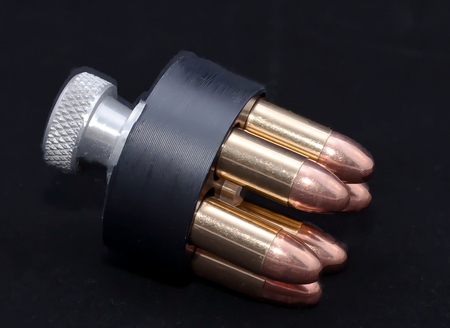 A loaded speed loader for a 38 caliber revolver on a black background Stock Photo