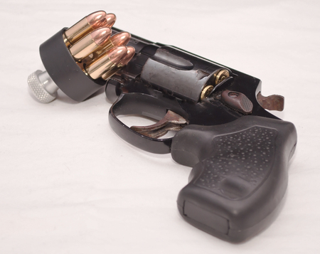 A black revolver with a loaded speed loader leaning against its barrel on a white background Stock Photo