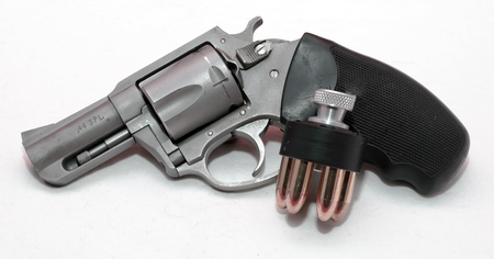 A stainless 44spl revolver with a loaded speed loader on a white background