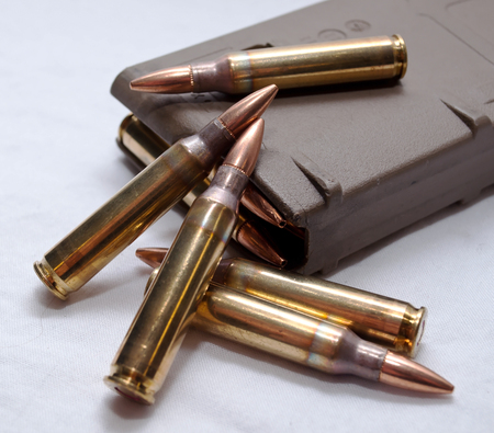 Several .223 caliber rounds and a loaded magazine on a white background Stock Photo