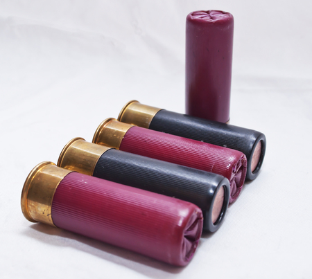 Five shotgun shells, four laying and one stood up on a white background 写真素材