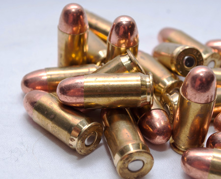 A pile of brass 45 caliber bullets with a white background