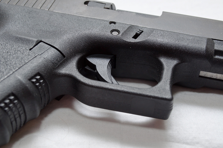 A close up of a black semi automatic pistol, showing the trigger, trigger guard, grip and ejection port 스톡 콘텐츠