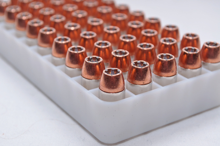 A plastic bullet container with .40 caliber hollow point bullets on a white background Stock Photo