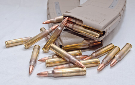 Two brown rifle magazines loaded with .223 rounds and several rounds laying next to them on a white background Stock Photo