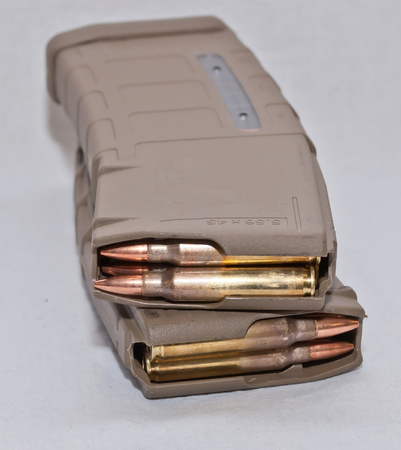 Two loaded .223 rifle magazines stacked on top of each other on a white background. The magazines are stacked in opposite directions from one another.