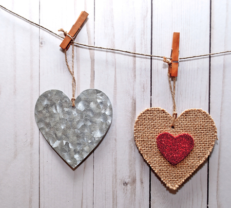 Two hearts, one silver and the other one brown with a smaller red heart in its center, hanging on a line in front of a white washed fence Stock Photo