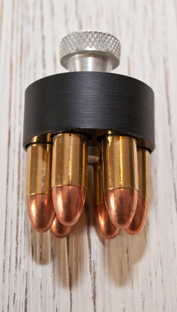A close up of a revolvers speed loader, loaded with six bullets and laying on a white wooden table Stock Photo