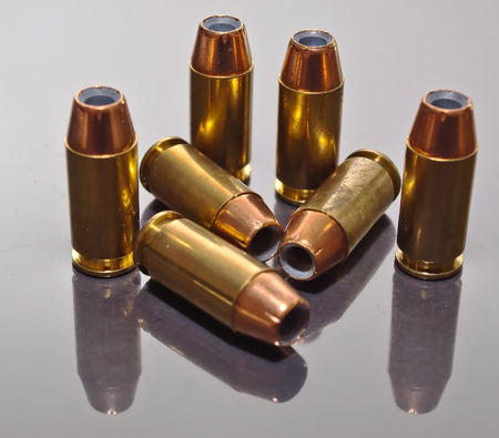 Seven 9mm hollow point bullets, with their reflections together on a glass surface