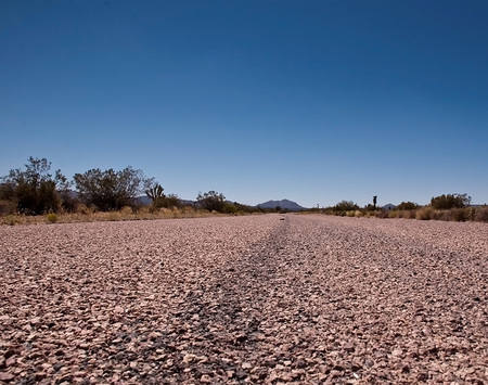 A close up view of a paved road in the Mojave desert in southern California under a bright blue sky Stock Photo