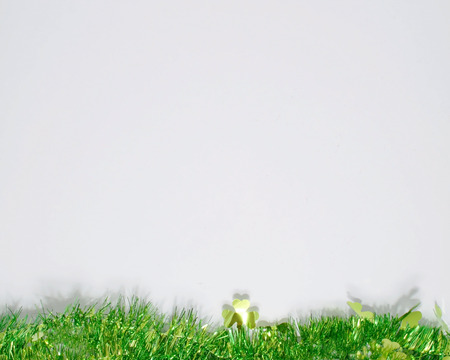A St Patricks day background with green grass and shamrocks at the bottom of the shot with a large white area for text or graphics