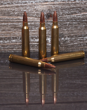 Five rifle bullets in front of a wooden background placed upon a reflective surface showing the bullets.