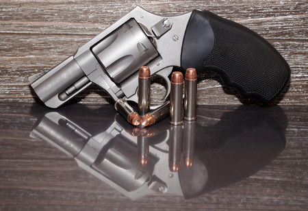 A stainless steel 357 magnum revolver with five bullets in front of it with a wooden background and all on a reflective surface