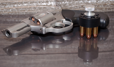 A loaded, stainless steel .357 magnum revolver with a black and silver loaded speed loader next to it on a reflective surface with a wooden background