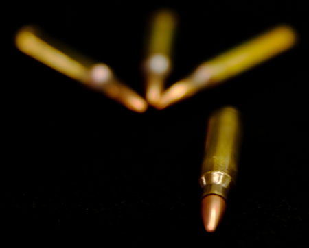 A .223 caliber round with three laying behind it slightly out of focus on a black background