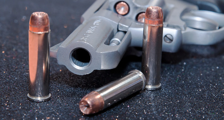 A loaded, stainless 357 snub nosed revolver with three bullets next to it, 357 Magnum is stamped into the barrel