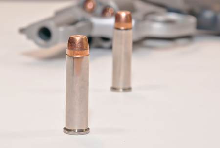 Two .357 magnum bullets with a stainless loaded revolver in the background