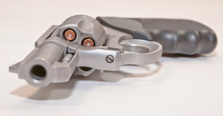 A .357 magnum revolver loaded with hollow point bullets shown laying on it's side with a white background